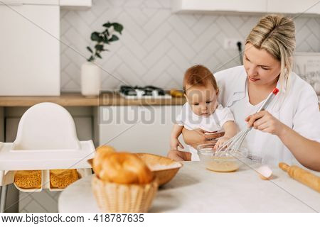 A Young Mother Holds Her Baby In Her Arms, Whips The Eggs With A Whisk And Prepares The Dough. Mom A