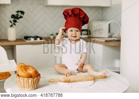 A Small Beautiful Child Dressed In A Cooking Cap Sits On The Table Next To The Dough And Rolling Pin
