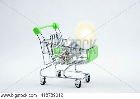 Purchase Of Electricity. Glowing Energy Saving Light Bulb  In A Shopping Cart. Save Electricity.