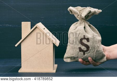 Hand Holds A Canvas Bag Full Of Money And A Wooden House On A Blue Background. The Concept Of Buying