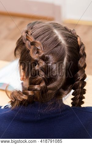 The Girls Hairstyle Is Braided In Two Braids With A Close-up Parting. Hair Styling Is Done With Hair