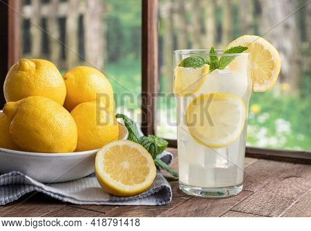 Glass Of Homemade Lemonade And Lemons On A Wooden Table By A Window With Rural Background Scene