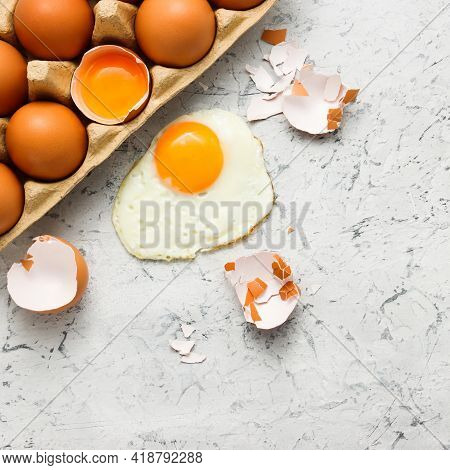 Raw Eggs In Cardboard Box With The Fried Egg And Eggshells Top View At The White Beton Background