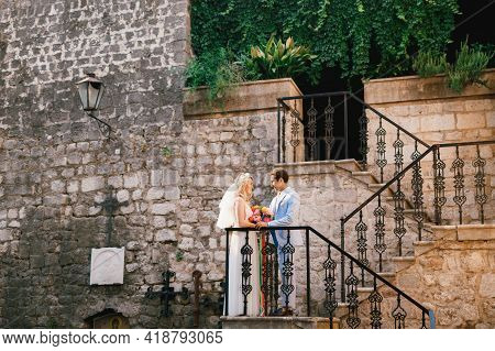 The Bride And Groom Stand On A Beautiful Staircase With A Wrought Iron Railing In The Old Town Of Pe