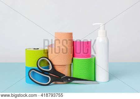 Rolls Of Kinesiology Tape For Athletes, Scissors And Antiseptic Bottle On White Background. Copy Spa