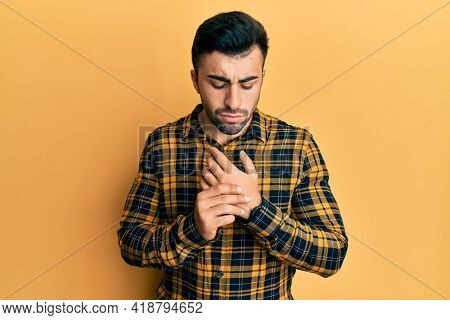 Young hispanic man wearing casual clothes suffering pain on hands and fingers, arthritis inflammation