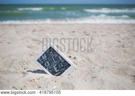 Berdyansk, Ukraine - 06.11.2020: Kindle Book Reader With White Frame And Grey Screen Of Letters Stic