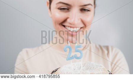 The Happy Woman Makes A Wish And Blows Out The Candles On The 25th Birthday Cake. Girl Celebrating B
