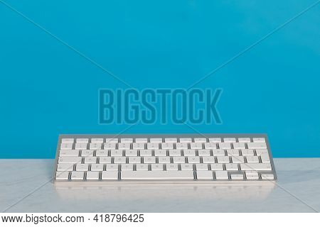 The Computer Keyboard Lies On The Desk And Above It Is A Blue Solid Background