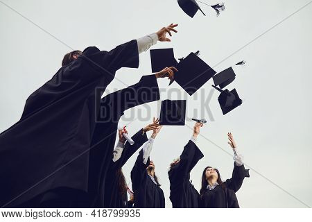 Graduates Toss Their Academic Hats Into The Sky During A Solemn Ceremony At The University.