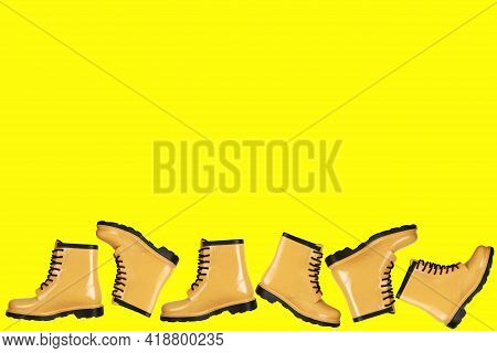 Creative Background With Yellow Rubber Boots At The Bottom On A Yellow Background.lots Of Women's Ru
