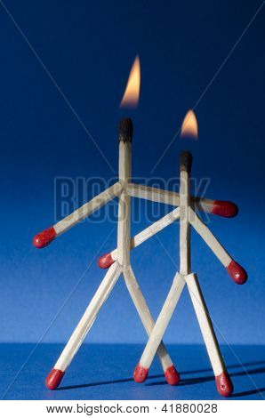 Couple of match people on fire and blue background