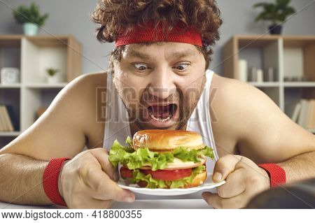Hungry Crazy Chubby Man In Sportswear Eating Fast Food Hamburger Portrait