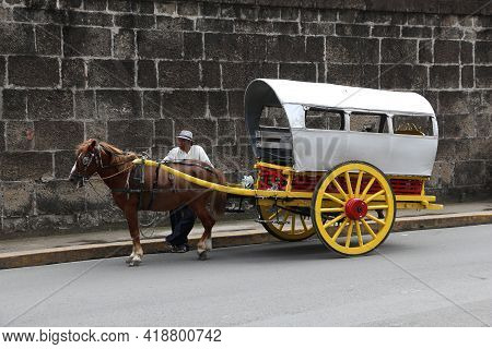 Manila, Philippines - November 25, 2017: Driver Stands By Horse Carriage In Intramuros District, Man