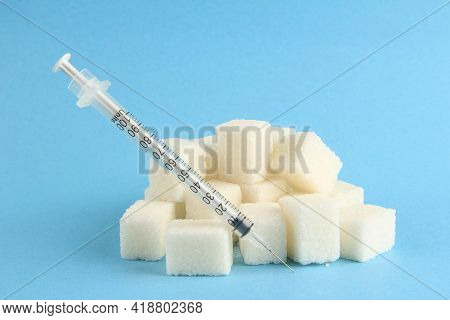 Against The Blue Medical Background, The Syringe Plunged Into The Sugar. Medical Concept Of Minimali