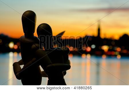 Wooden Mannikin Couple Embracing And Looking At The City