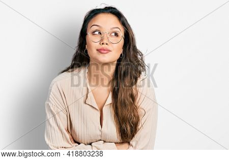 Young hispanic girl wearing casual clothes and glasses smiling looking to the side and staring away thinking.