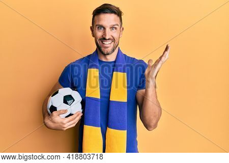 Handsome man with beard football hooligan cheering game holding ball celebrating achievement with happy smile and winner expression with raised hand