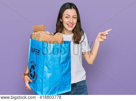 Young beautiful woman holding recycling wastebasket with paper and cardboard smiling happy pointing with hand and finger to the side