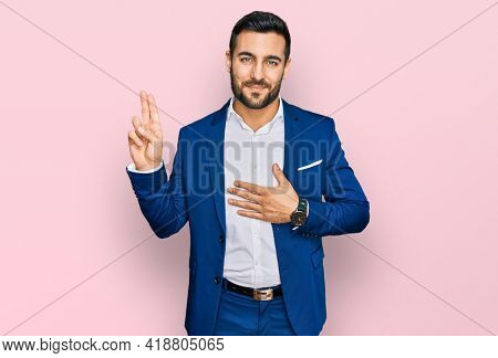 Young hispanic man wearing business jacket smiling swearing with hand on chest and fingers up, making a loyalty promise oath