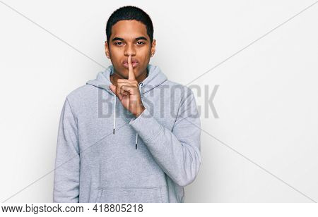 Young handsome hispanic man wearing casual sweatshirt asking to be quiet with finger on lips. silence and secret concept.