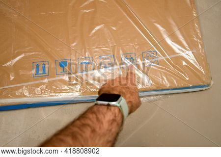 Pov Male Hand Showing To Cardboard Package Covered With Plastic Film With Multiple Pictograms - Atte