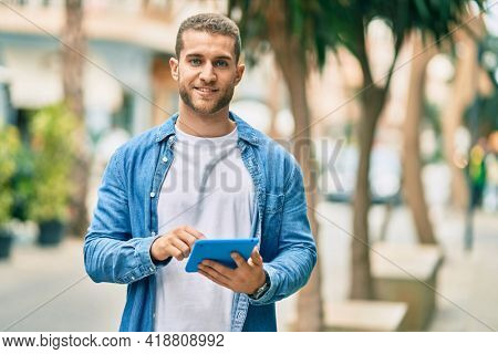 Young caucasian man smiling happy using touchpad at the city.