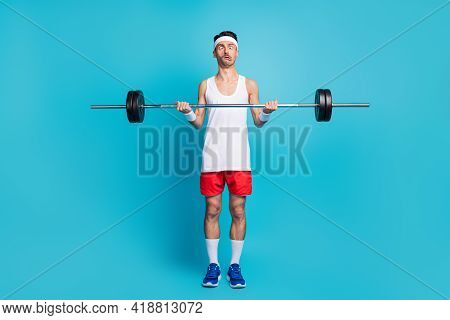 Photo Of Young Sportsman Lift Heavy Barbell Grimacing Exercise Bodycare Isolated Over Blue Color Bac