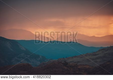 Atmospheric Landscape With Silhouettes Of Mountains With Trees On Background Of Orange Dawn Sky. Col