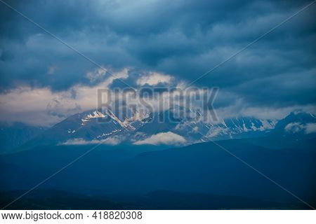 Atmospheric Mountain Landscape With Great Snowy Mountains In Low Clouds And Sunset Cloudy Sky. Aweso