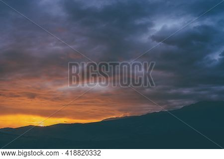 Atmospheric Landscape With Silhouettes Of Mountains With Trees On Background Of Vivid Orange Blue Vi