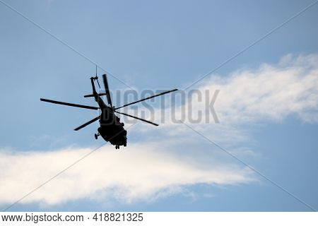Military Helicopter Silhouette In Flight On Background Of Blue Sky And White Clouds. Bottom View, Ai