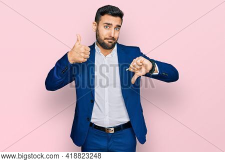 Young hispanic man wearing business jacket doing thumbs up and down, disagreement and agreement expression. crazy conflict