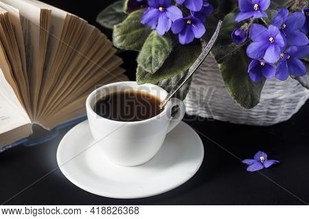A Cup Of Black Coffee With A Book And A Violet Flower On The Table.