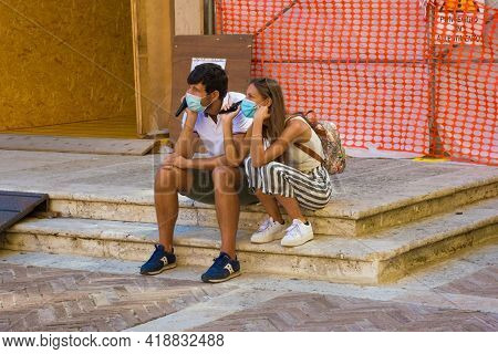 Pienza, Italy - September 6th 2020. Two Tourists Wearing Masks Listen To An Audio Guide In The Histo