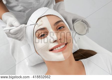 Front View Portrait Of Smiling Young Brunette Woman Lying On Procedure For Face In Beautician. Conce
