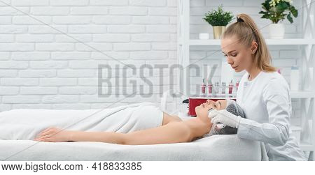 Side View Of Young Beautiful Woman Lying On Sofa On Procedure For Face In Young Cute Beautician. Con