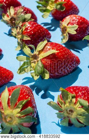 Several Strawberries Placed On A Blue Background Following A Pattern And Illuminated By Natural Ligh