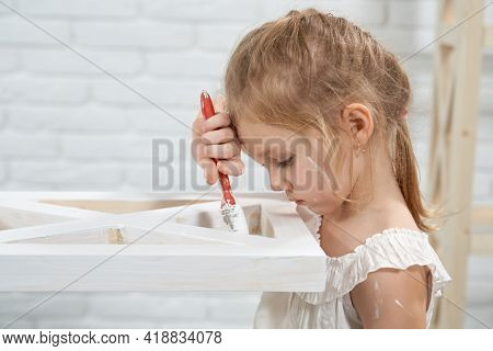 Concept Of Cute Little Girl Painting With Brush Wooden Rack In White Color At Home. Concept Of Impro