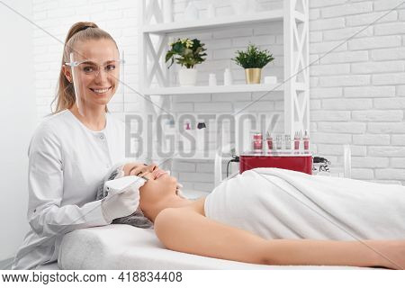 Side View Of Smiling Young Beautician In Protective Mask Doing Cleaning Procedure With Special Moder