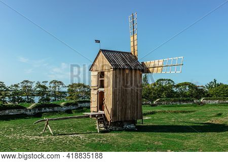 Beautiful Folk Architecture.old Traditional Wooden Windmill In Estonia Against Blue Sky.abandoned Ic