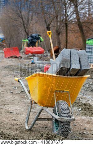 Curb Concrete Blocks Lie Inside A Construction Wheelbarrow At A Construction Site On A Paving Paveme