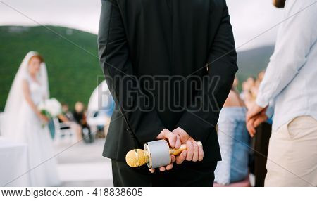 The Host At A Wedding Party Stands And Holds A Microphone Behind His Back, Close-up