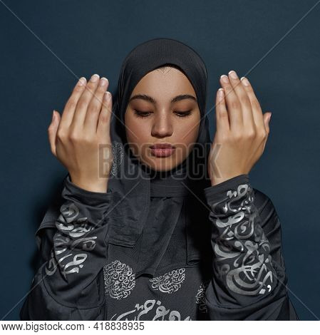 Selective Focus On Young Arabian Woman Wearing Traditional Hijab And Bare Hands In Front Of Her Face