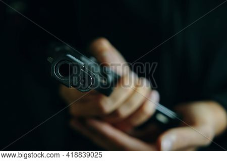 Muzzle Of Pistol Close-up. Guy Reloading Gun. Weapon Ammunition. Firearms In Hand On Dark Background