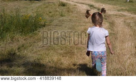 Little Girl Running By Country Road At Rural Landscape In Summer. Her Funny Ponytails Jump In Air. S