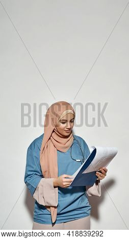 Pretty Young Arabian Girl Doctor In Hijab Looking Into Notepad While Posing On Light Background With