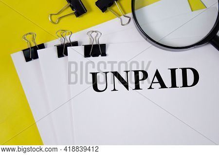 Unpaid Word Written On White Paper And Yellow Background With Magnifier