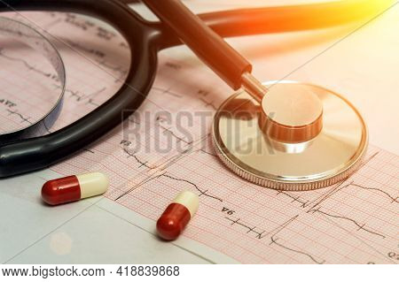 A Medical Stethoscope Lies On A Cardiogram Chart And A Pill Close-up. Medical Care, Prevention, Dise