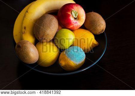 Ripe Colorful Whole Fruits: Apples, Kiwi, Edible Yellow Lemons, Bananas In A Plate With Spoiled Lemo
